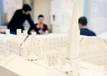 Scale model of a building with students in the background